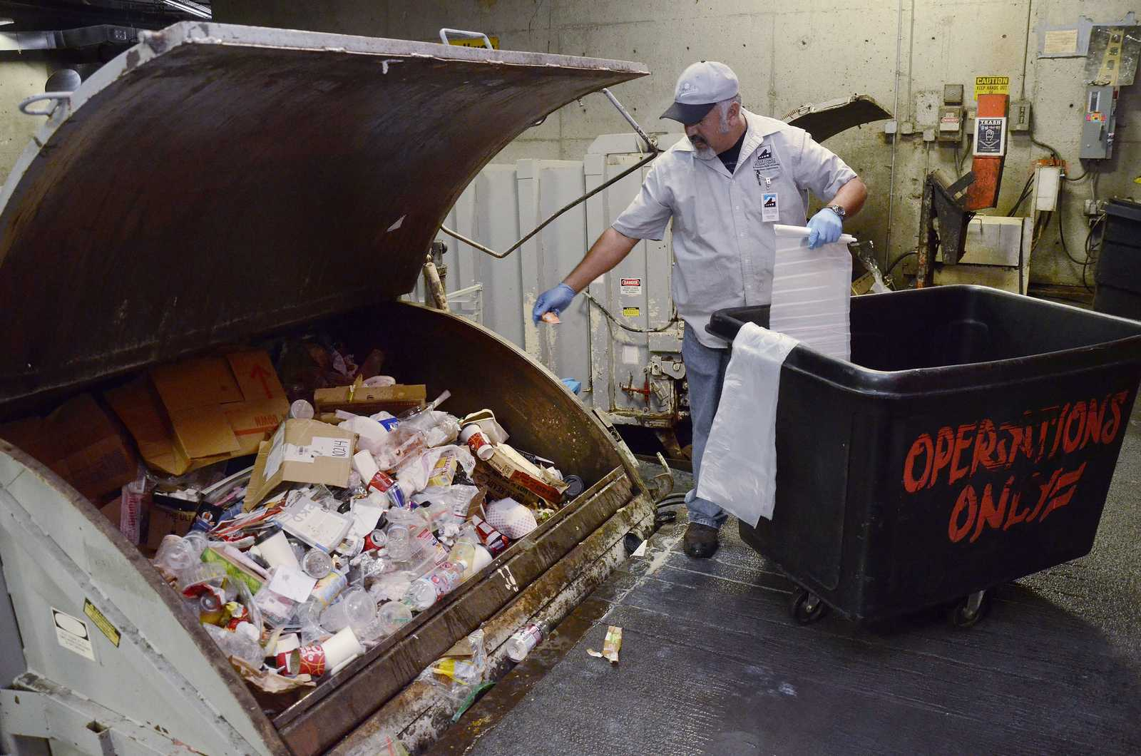 Agustin Cazares, who has been working at SF State for 33 years, empties the compost, recycling and waste beneath the Cesar Chavez Student Center in a zero waste effort on Tuesday, Sept. 3, 2013. Photo by Virginia Tieman / Xpress