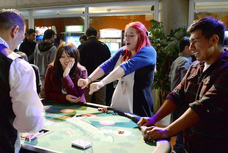 Sarah Pishney, special events assistant for ASI, celebrates after getting 21 during a round of blackjack at Casino Night, as ASI sponsored event, held in the bottom of the Cesar Chavez Student Center at SF State on Friday, Nov. 8, 2013. Photo by Virginia Tieman / Xpress