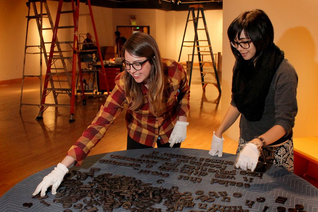 Senior art history major Mary Slinkert (left) and Maricelle Gonzales, senior studio art major (right), assemble letters to form phrases which will be placed on the floor as part of an exhibit in the Printmaking Show in the Fine Arts Building Room 238 Friday, Feb. 7. Slinkert and Gonzales are students in the Exhibition Design class responsible for displaying the works. Photo by Tony Santos / Xpress