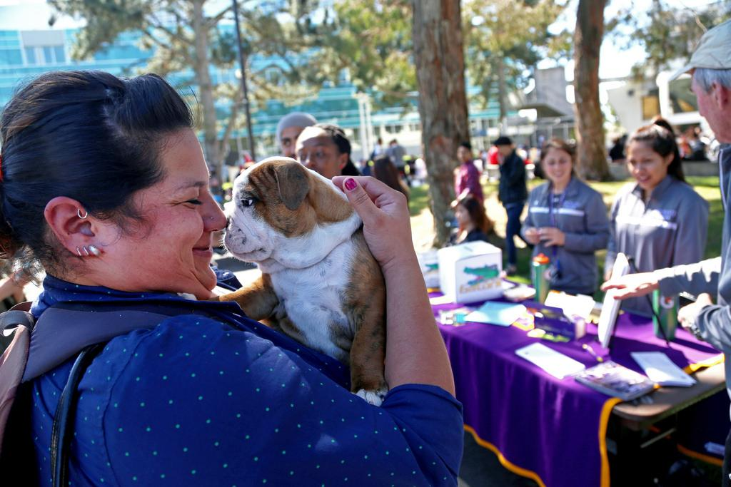 Jillian Picaso, a communicative disorders grad student, holds Chunky the  at the Founders Day event at the Cesar Chavez Center Tuesday, March 18. For $1, spectators could hold the puppy. Money raised goes towards the athletic department. Photo by Rachel Aston / Xpress