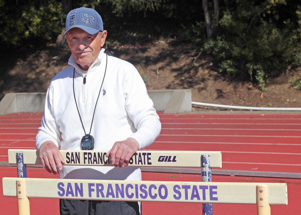 Volunteer Coach Morris Lozovatskiy stands on the track at Cox Stadium Monday, March 17. Photo by Jenny Sokolova / Xpress