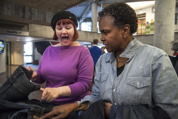 Heather Shetrawski (left) reacts to discounted jean prices while Leslie Bilbro, a Goodwill volunteer, assists her during Levi's Mendables Earth Day event sponsored by Goodwill in Cesar Chavez Student Center at SF State Tuesday, April 22. Photo by Jessica Christian / Xpress