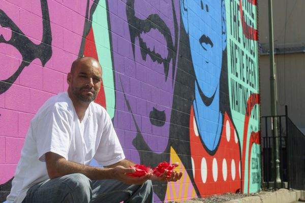 """Jeff Duncan-Andrade, Ph.D, a 43-year-old Associate Professor of Raza Studies at SF State, poses for a photo at Thomas L. Berkley Way (20th Street) and Telegraph in Oakland in front of the mural """"We Are The Ones We've Been Waiting For"""" by Jessica Sabogal, a Colombian American graffiti artist. Photo taken in Oakland, Cali. Friday, Sept. 26, 2014. Amanda Peterson / Xpress."""