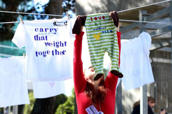 Kandice Khopp hangs a onesie during the Clothesline Project at SF State Monday, Oct. 27, 2014. Henry Perez/Xpress.