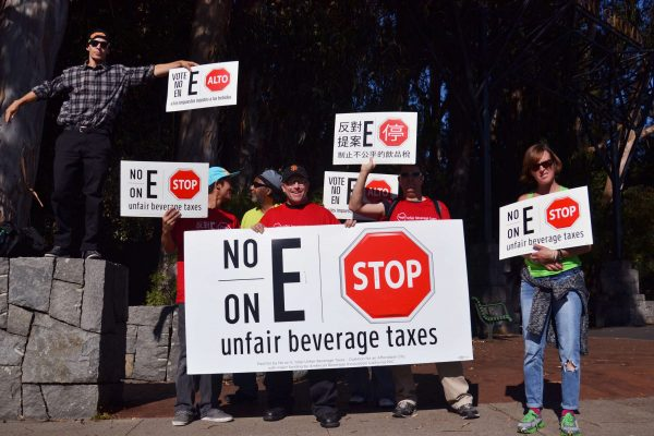 Paid volunteers for the No-on-E campaign hold signs up on the corner of Sloat Boulevard and 19th Avenue, opposing the soda tax being voted on that day Tuesday, Nov. 4, 2014. Helen Tinna/Xpress.
