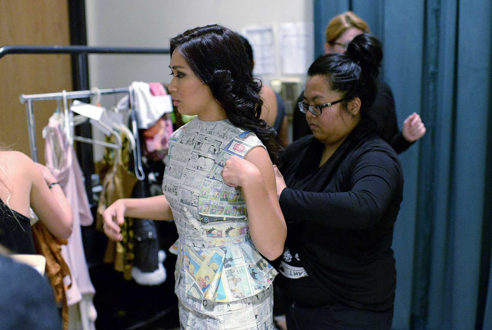 Kris Roberto, wearing a design in the Zero Waste Pledge portion of the show made by Maria Cabanban, changes clothes before walking the runway during the