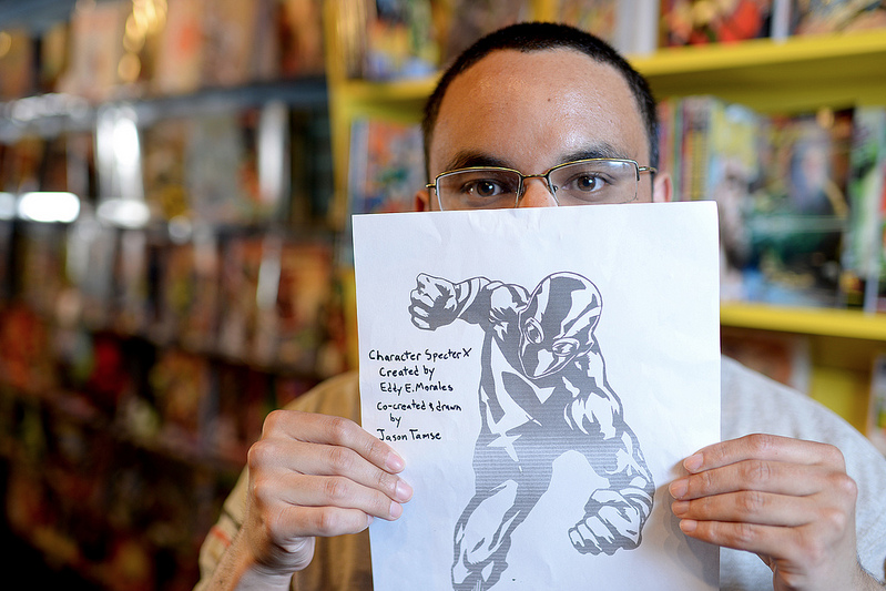 "Eddy Enrique Morales, alumnus of SF State with a BA in drama, holds up a drawing of Specter X, a character he created and calls ""San Francisco's first and very own Latino superhero."" Morales aims to have his first comic, featuring Specter X, come out early 2014 with the help of funds he received through a fundraising website and the San Francisco community. Photo by Virginia Tieman / Xpress"