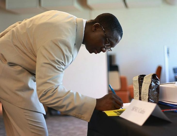 Tamba Sellu, Chico State alumni, writes his name at SFSU Cafes' booth at the Hospitality Career Fair Thursday, March 20, 2014. Photo by Ryan Leibrich / Xpress