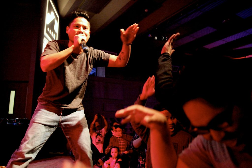 Nomi of hip hop duo, Power Struggle, preps to high five an audience member during Mula Sa Ugat: From the Roots, SF State's 11th annual celebration in honor of the Filipino community mural on campus, on Thursday, April 3. Photo by Lorisa Salvatin / Xpress