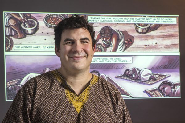 """Professor of History Trevor Getz, poses in front of scenes from his scholarly graphic novel """"Abina and the Important Men,"""" in Humanities building Tuesday, April 1. Getz recently created a company called Motion Education Applications Inc. to apply this graphic model to other areas of study."""