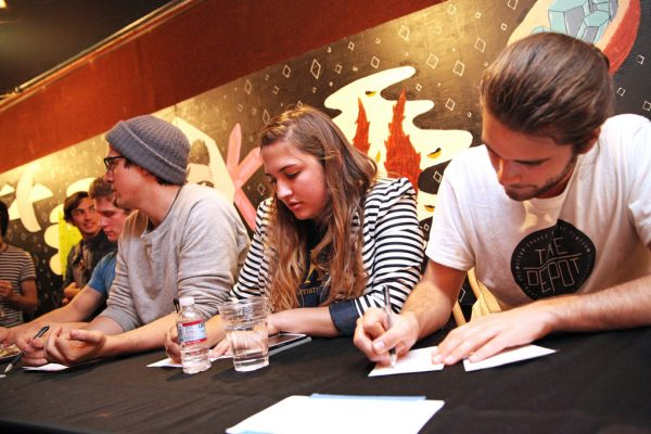 (From left) Battle of the Band Judges, Cassidy Martin, Silver Friedline, and Tanner Reyes start filling out their score sheets before the show begins in The Depot Wednesday, Apr. 9. Judges scored each band on musicianship, crowd response, stage presence and energy. Photo by Lorisa Salvatin / Xpress
