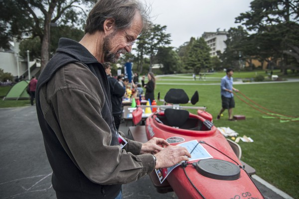 Patrick Tierney, professor of recreation, parks, and tourism, places a flyer for an accessible kayaking trip on Lake Merced put on by Ryan Fetzer during SF State's Accessible Adventure Day in Malcom X Plaza Tuesday, April 15. Photo by Jessica Christian / Xpress