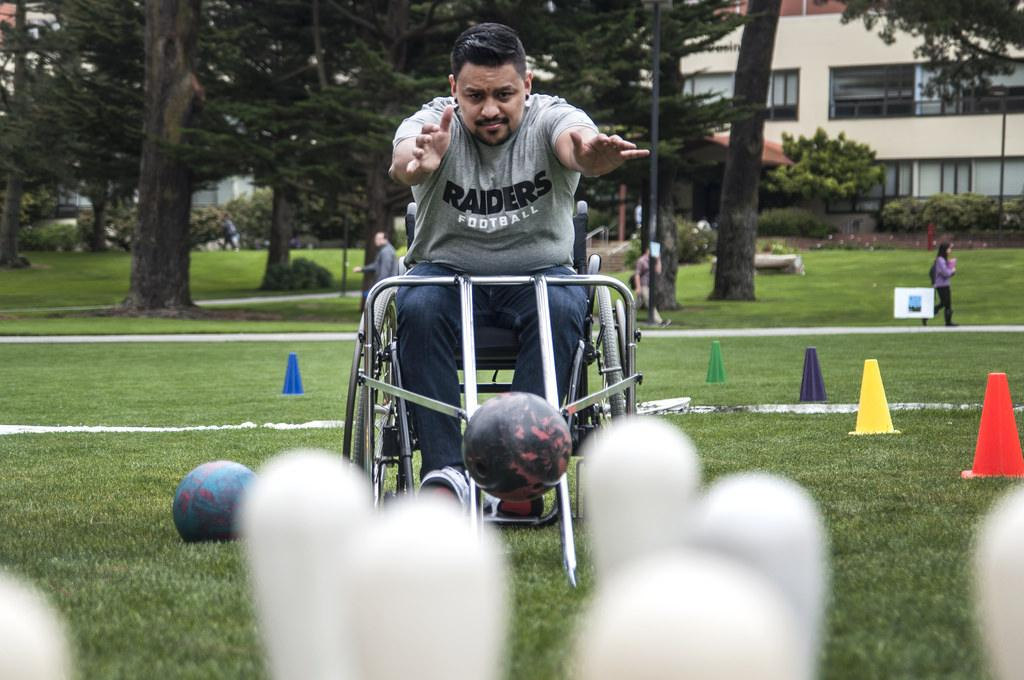 Alfredo Andrade, a kinseology major, gets a hands on experience on what it's like to be a wheelchair-user whie playing accessible bowling on the lawn at Malcom X Plaza during SF State's Accessible Adventure Day Tuesday, April 15. Photo by Jessica Christian / Xpress