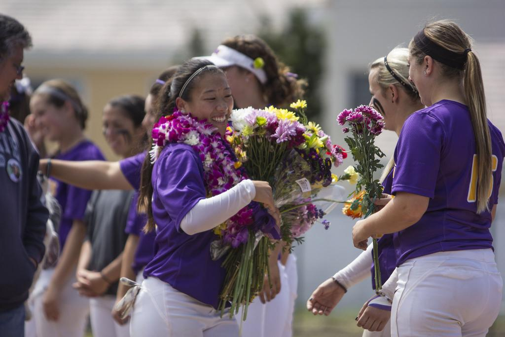 SF State Gator's Kelsey Murakami (13), hugs her teammates as they give her flowers during the senior celebration ceremony before the first game of a double header against the Sonoma State Seawolves at SF State Sat. April 26.