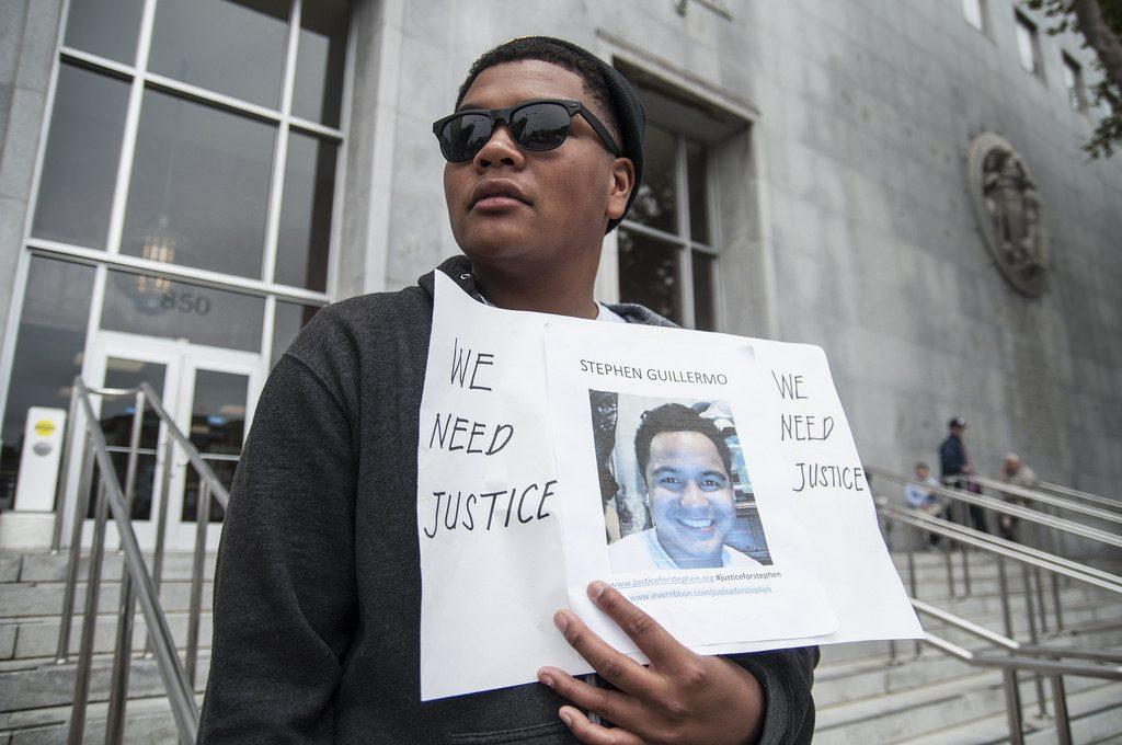 Joshua Connley stands outside of the Hall of Justice building Thursday, May 8 holding a sign for his cousin in protest, asking the district attorney's office to file charges against the man accused of shooting him in the early morning hours Saturday, May 3. Photo by Jessica Christian / Xpress