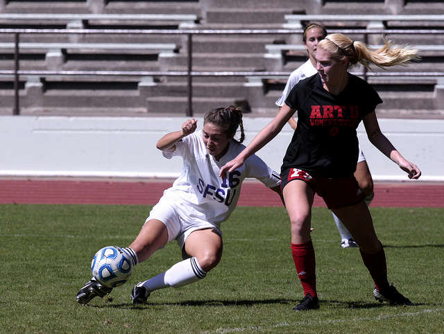 Alex Palomino, left, number 16 of SF State kicks the ball around Maddie Shelton, of the Academy of Art Soccer team at Cox Stadium at SF State, on Sunday, Sept. 7, 2014. SF State won the game 2-1, scoring the game winning goal within 15 minutes left in the game.