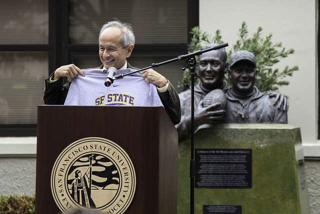 SF State president Leslie E. Wong holds up one of the new athletic t-shirts in Don Nasser Family Plaza during the reopening ceremony of the newly remodeled gymnasium on Thursday, Sept. 11, 2014.