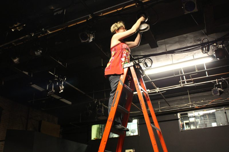 Amanda Ortmayer hangs the finishing touches in EXIT! Theater in preparation for the SF Fringe Festival.