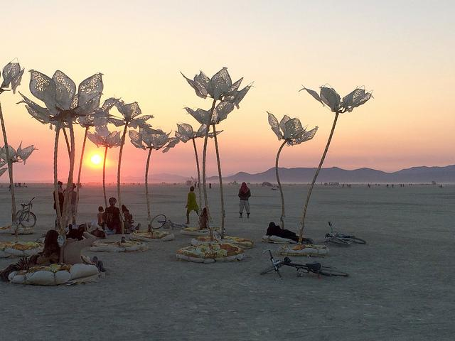 Burning Man participants watch the sunrise from the comfort of padded seating on the art installation