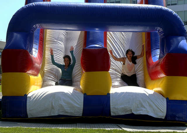 Paola Cerna and Monica Villa slide down the inflatable slide at The 3rd Annual Kick Off presented by ASI held the event at Cesar Chavez Plaza at SF State Thursday, September 4, 2014 in San Francisco, Cali.