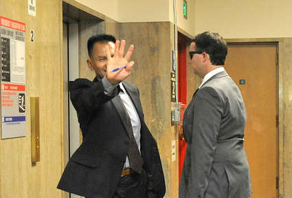 Mark Landis's attorney, Thanh Ngo, attempts to block his client from the cameras after his trial in courtroom Dept. 17 at the San Francisco Hall of Justive, Tuesday Sept. 9, 2014.