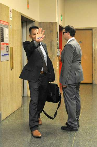 Mark Landis's attorney, Thanh Ngo, attempts to block his client from the cameras after his trial in courtroom Dept. 17 at the San Francisco Hall of Justive, Tuesday Sept. 9, 2014. Photo by Sara Gobets.