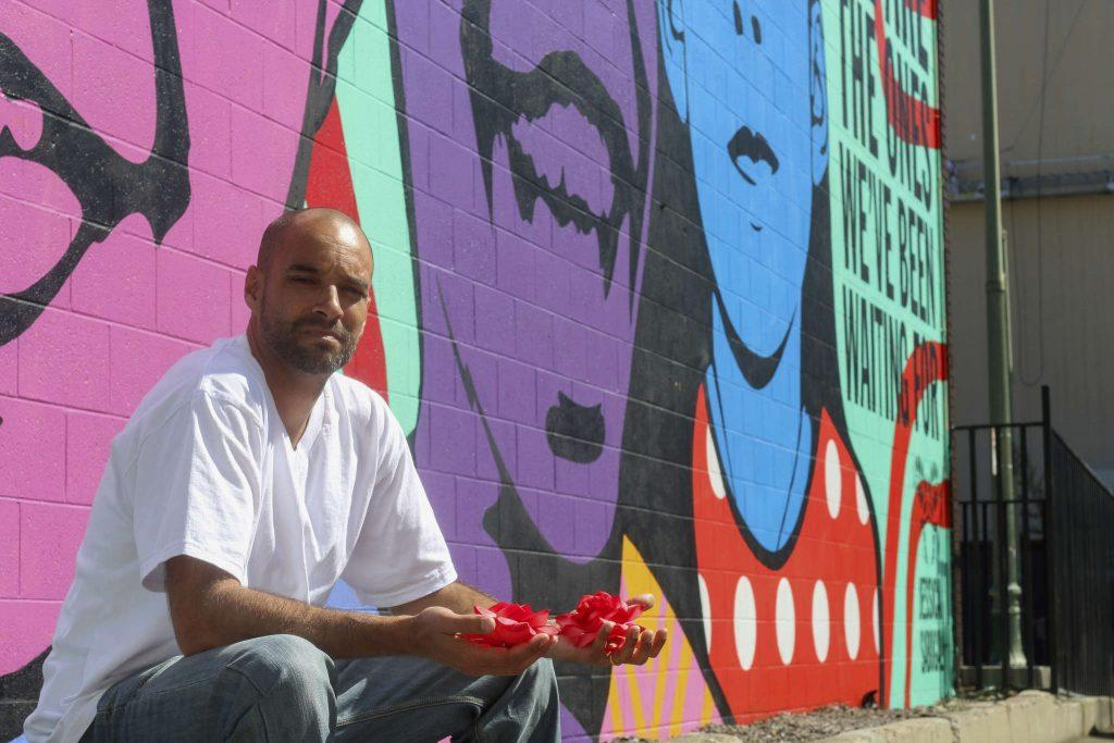 Jeff Duncan-Andrade, Ph.D, a 43-year-old Associate Professor of Raza Studies at SF State, poses for a photo at Thomas L. Berkley Way (20th Street) and Telegraph in Oakland in front of the mural