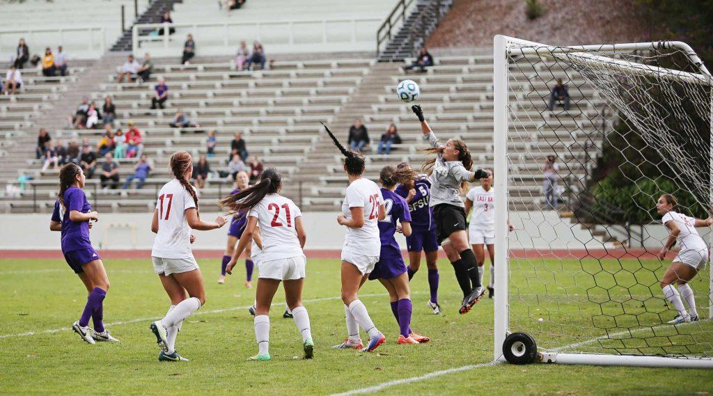 Cal State East Bay Pioneer goal keeper Briana Scholtens, #1, punches the ball out of danger after a SF State Gator attempt on goal at Cox Stadium on Sunday, Sept. 28, 2014.