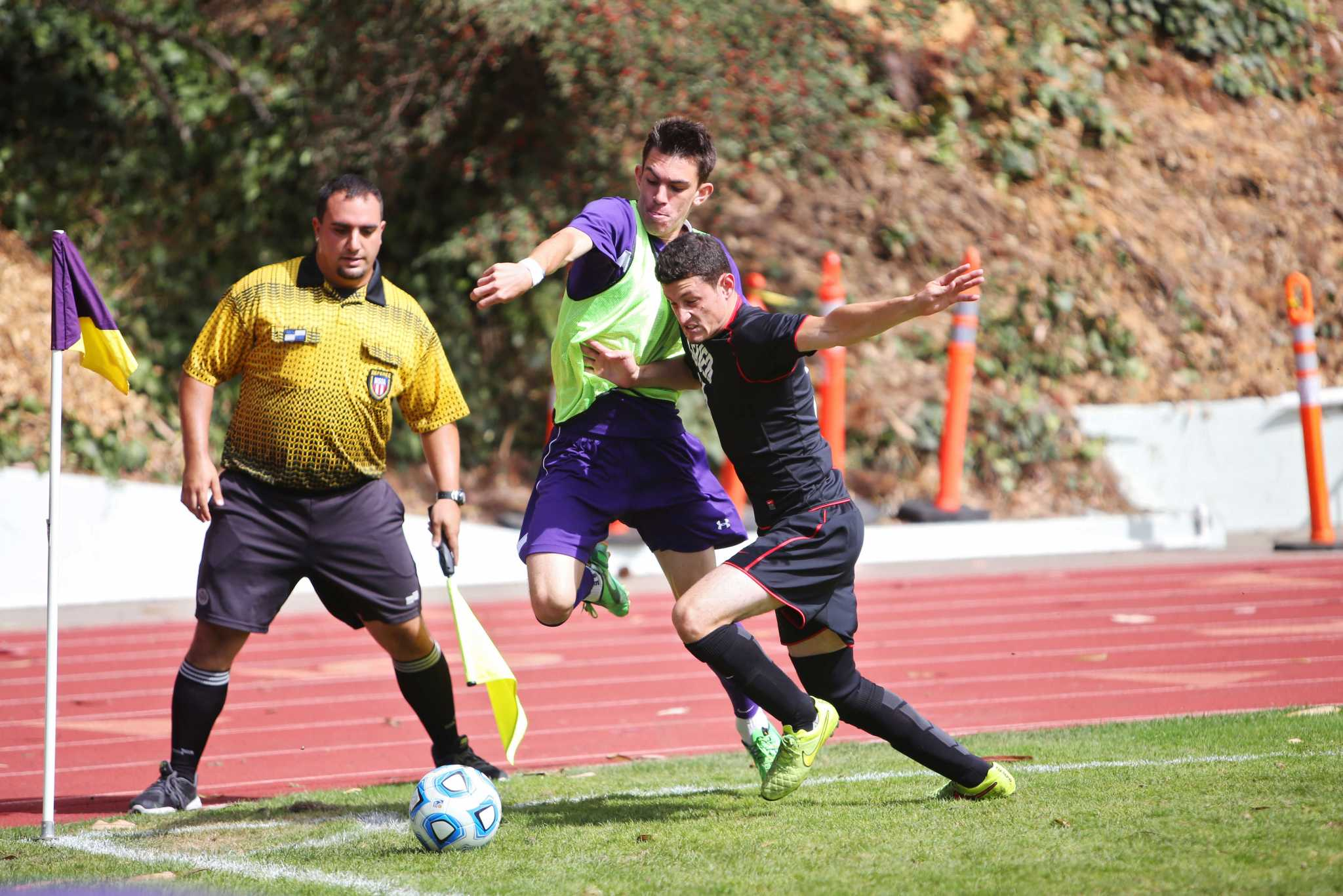 SF State Gator midfielder Sam Merritt, #10, fights for a ball in the corner against Cal State East Bay player Steven Henry, #25, at Cox Stadium on Sunday, Sept. 28, 2014. Sara Gobets / Xpress.