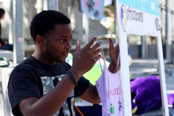 Shawn McGriffin takes a picture after painting a tee shirt for the Clothesline Project at SF State Monday, Oct. 27, 2014. Henry Perez/Xpress.