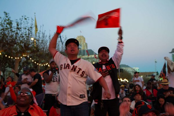 Al Enriquesz and Jesus Espinoza celebrate a San Francisco Giants hit in the fourth Inning during Game 7 of the World Series in the Civic Center Plaza in San Francisco, Calif., Wednesday, Oct. 29, 2014. Eric Gorman/Xpress.