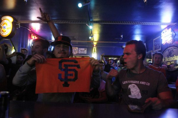 """Juan """"J.P."""" Gonzalez, a graduate student, shows off his Giants pride while watching the SF Giants Wild Card game against the Pittsburgh Pirates in the Pub at SF State Wednesday, Oct. 1, 2014. Daniel Porter / Xpress."""