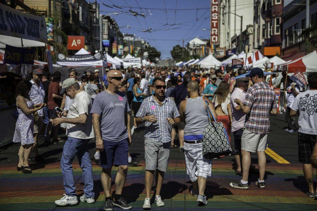 Fair attendees walk over the Castro neighborhood's newly installed rainbow crosswalk during the Castro Street Fair in San Francisco Sunday, Oct. 5, 2014.