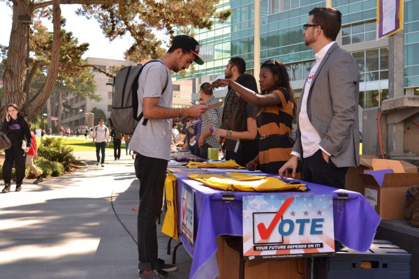 History major Joseph Scimonelli registers to vote at the campus government and community relations table Monday, Oct. 13, 2014. The event was intended to encourage students who have not yet registered to participate in the November election. Helen Tinna / Xpress.