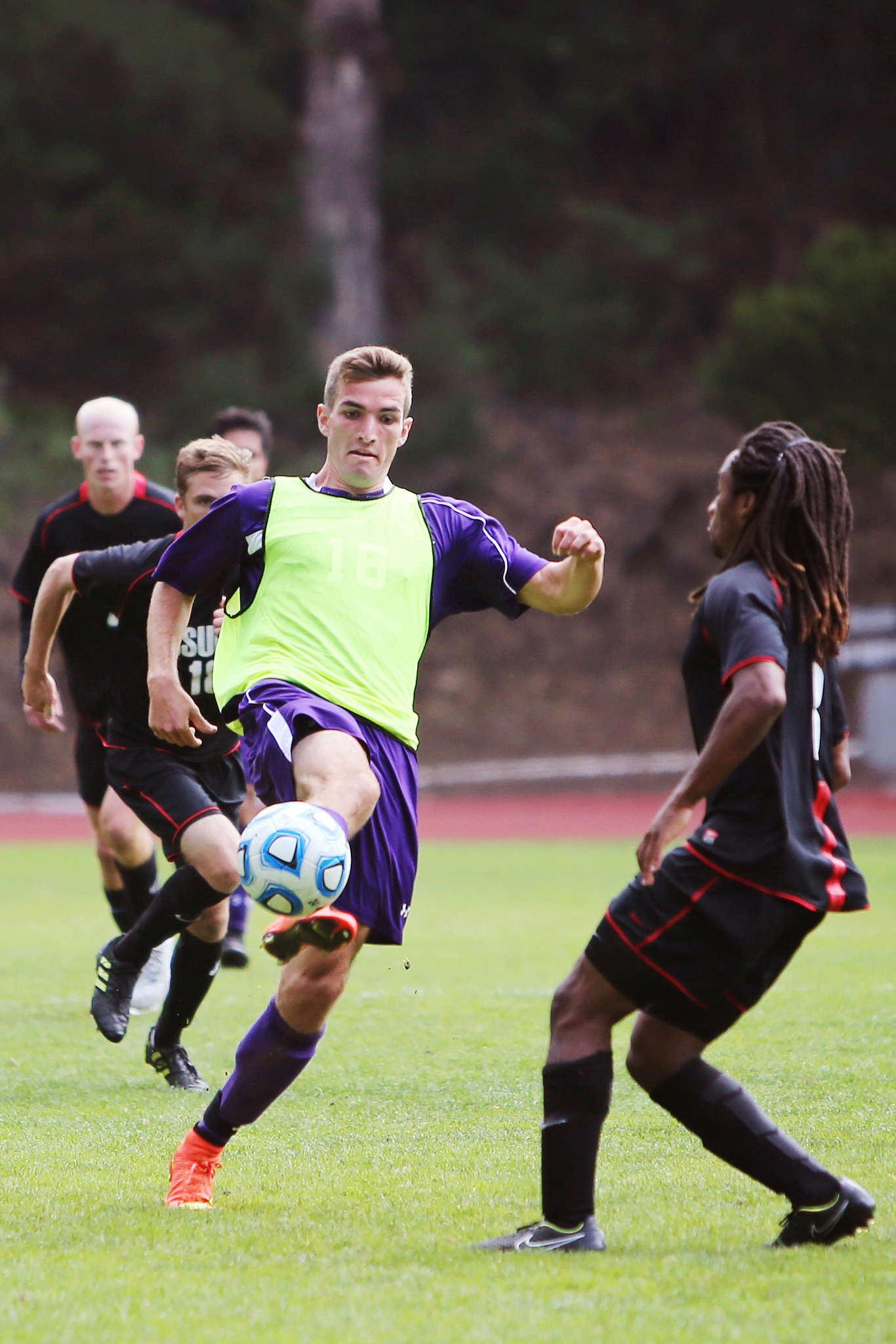 SF State Gator forward Cameron DeJong, # 16, volleys the ball out of the air away from advancing Cal State East Bay players, Kellen Crow, #15, and Arthur Ethel, #3, at Cox Stadium on Sunday, Sept. 28, 2014.