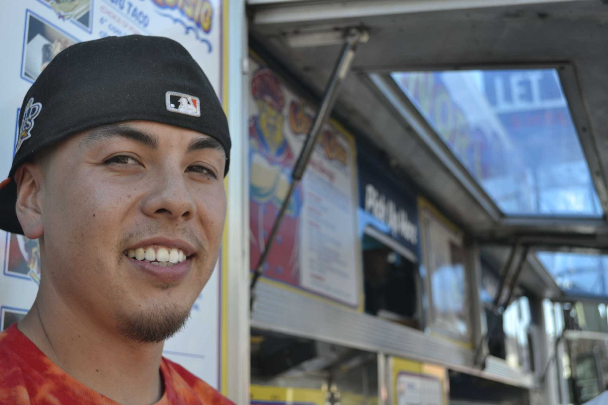 Sf State alumnus and co-founder of Señor SiSig Evan Kidera takes a break from his busy day to pose for a photo in front of his truck at the Soma Street Food Park Friday afternoon, Oct. 3, 2014.