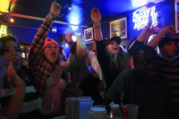 Angie Kanierwaski (left in orange beanie), a junior sociology major, and Anya Komisaryk (right in baseball hat), a senior Broadcasting and Electronic Communication Arts major, celebrate as the Giants win Game 1 of the World Series against the Kansas City Royals at the Pub at SF State Tuesday, Oct. 21, 2014. Daniel Porter / Xpress.