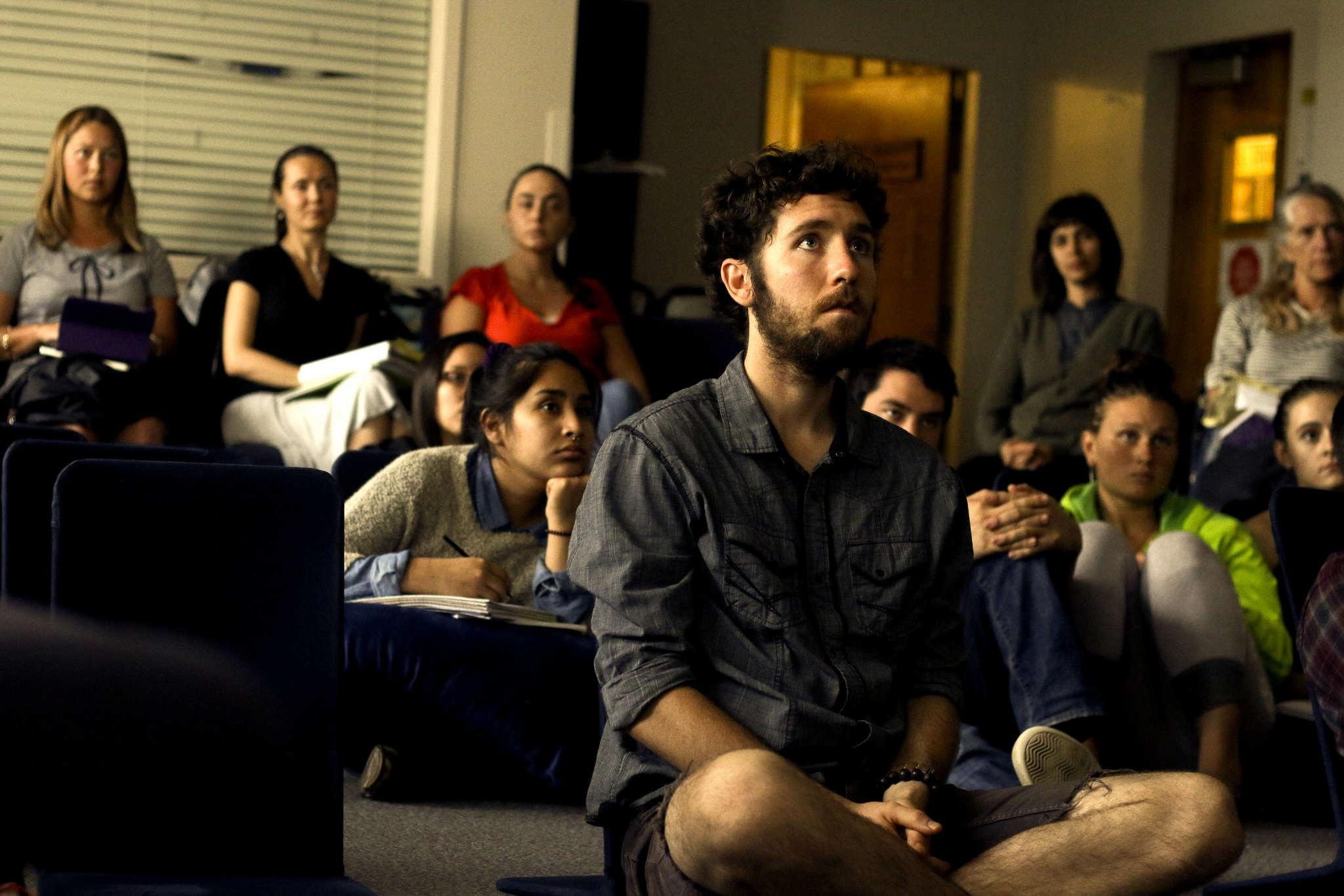 Nick Moore, 26, watches a film at the first Food Awareness Month meeting at SF State in HSS 306 Monday, Oct. 6, 2014.