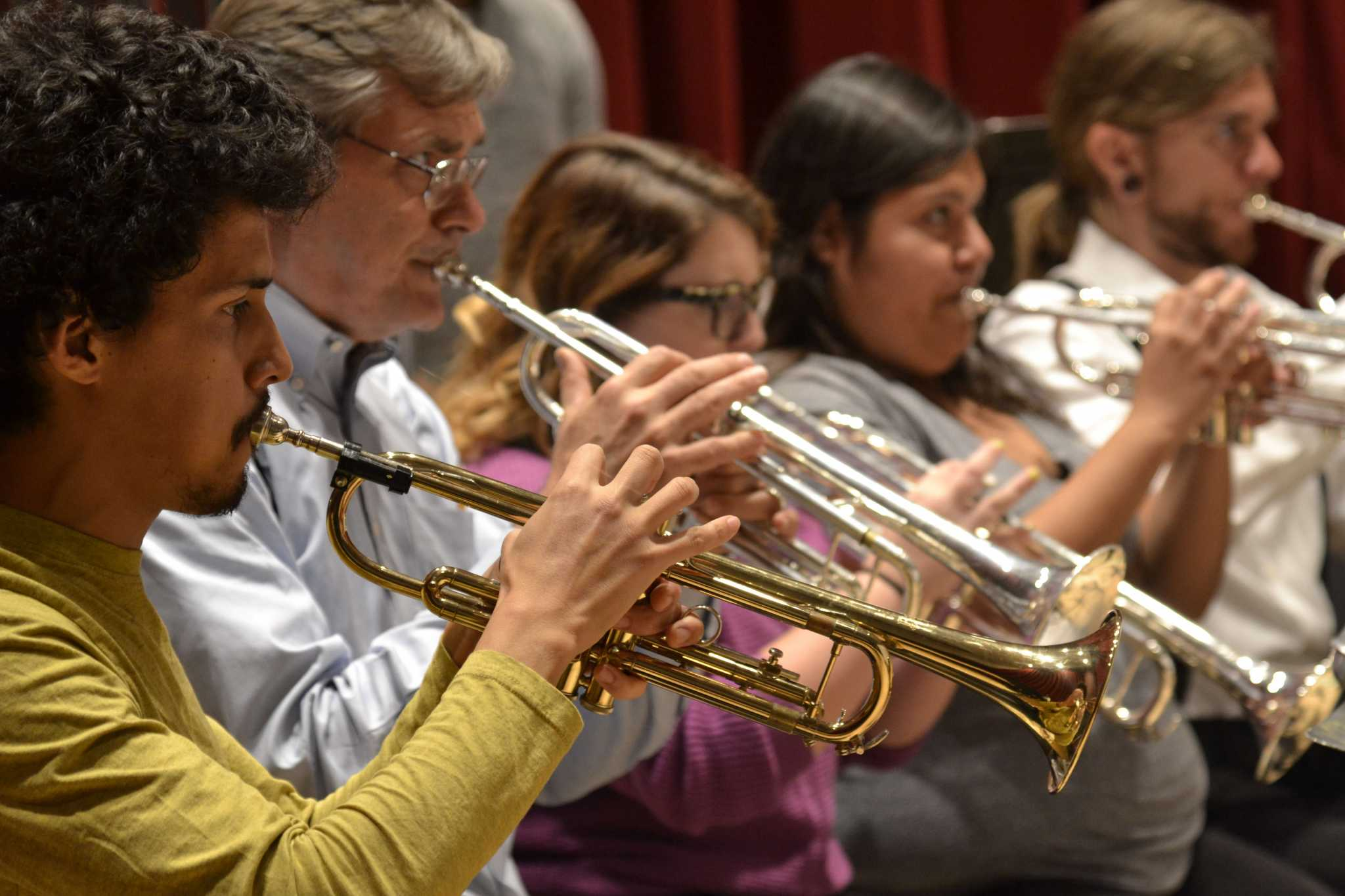 The trumpet section plays during a rehearsal with the SF State Wind Ensemble in preparation for