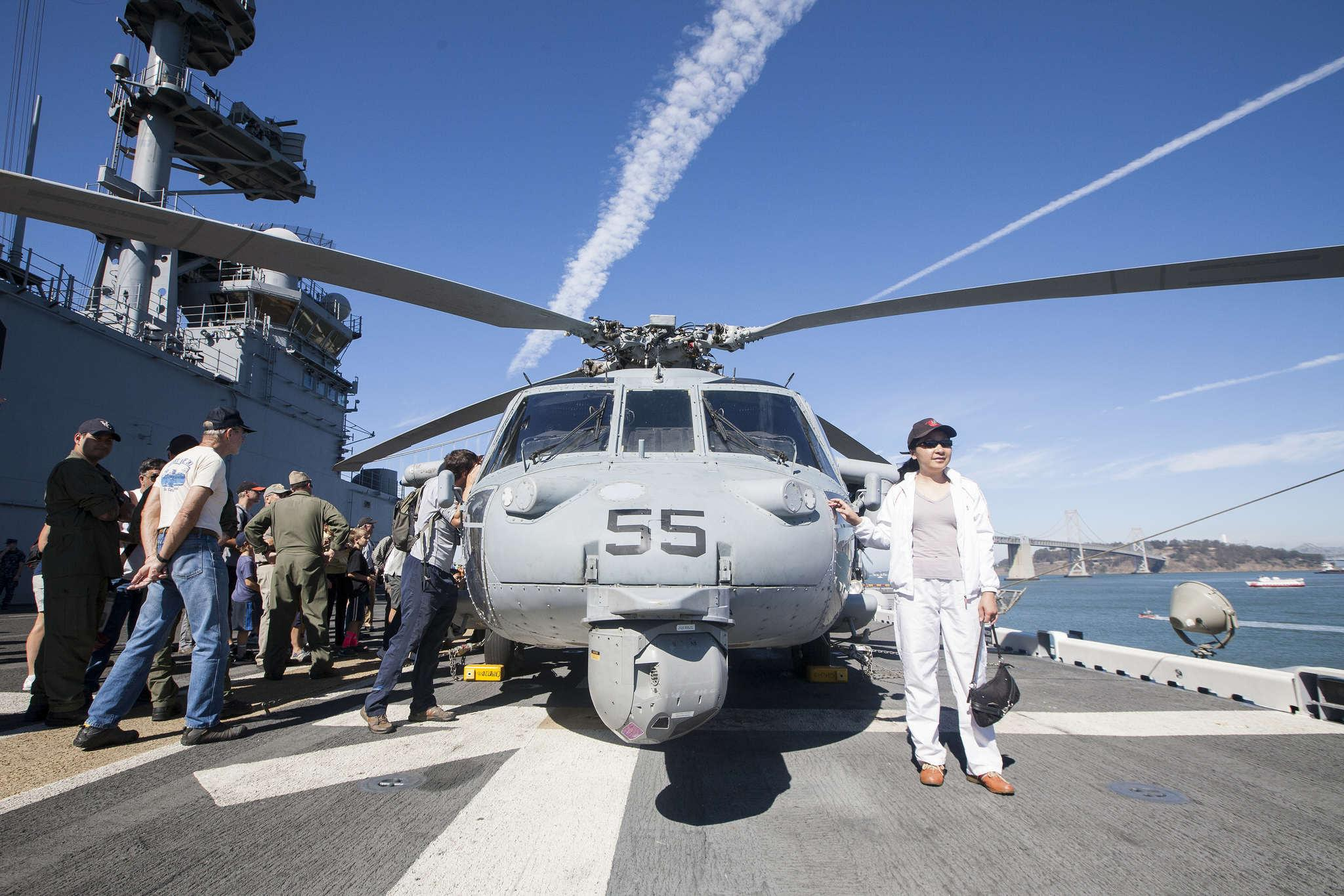 Mandi Yan (right) poses for a photo next to a MH-60S helicopter during a tour onboard the USS America Monday Oct. 13, 2014.