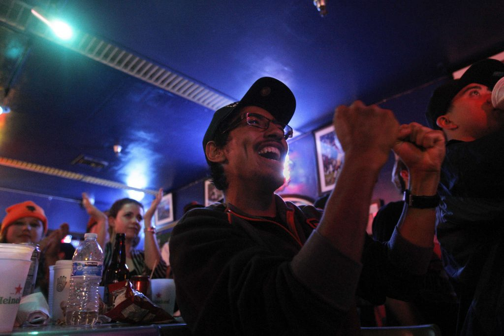 Juan Santamaria, a senior Latin studies major, cheers for the Giants during the bottom of the ninth inning during Game 1 of the World Series with the SF Giants against the Kansas City Royals at the Pub at SF State Tuesday, Oct. 21, 2014.