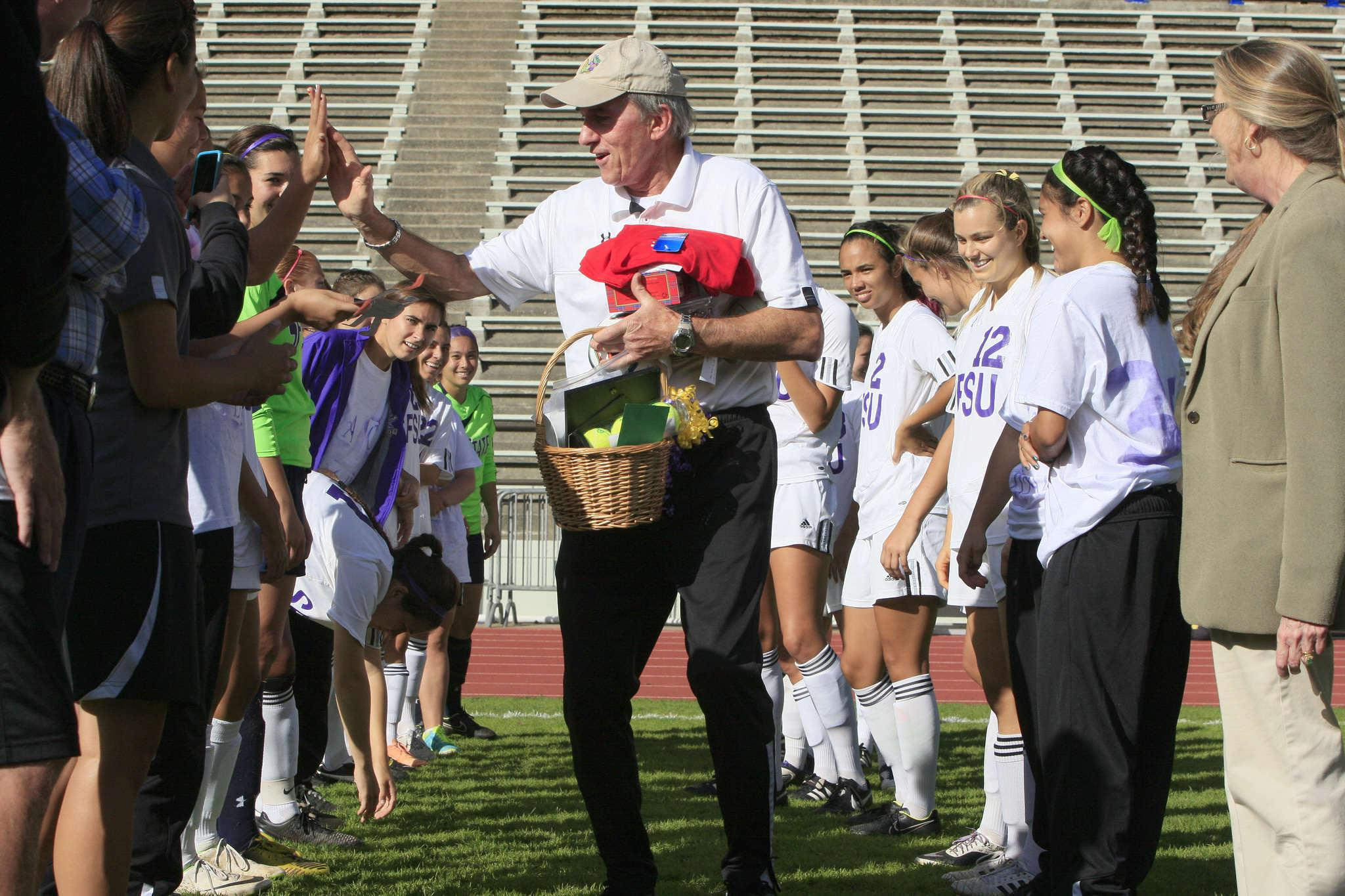 Jack Hyde high-fives a player from the girls soccer team, while he holds presents the team got for him. Coach of the women's soccer team at SF State, Jack Hyde, is retiring this season, so the team made Oct. 22 Coach Jack Hyde Day, right before the girls soccer team at Cox Stadium in San Francisco, Calif., on October 22, 2014.