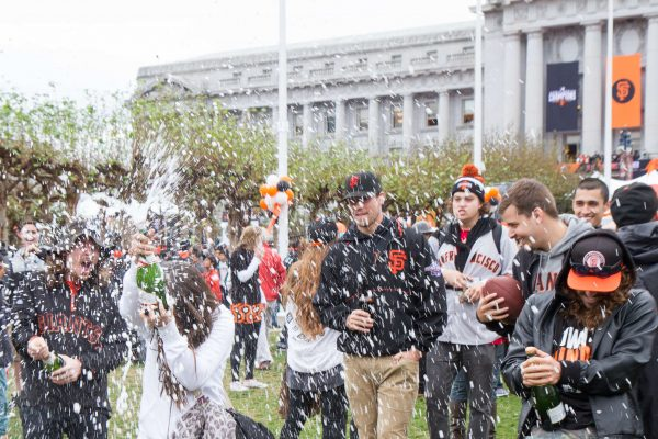 Sandra Correia and her friends spray champagne in celebration of the San Francisco Giants World Series victory during the parade in the Civic Center outside of city hall Friday, October 31, 2014. Eric Gorman/Xpress.