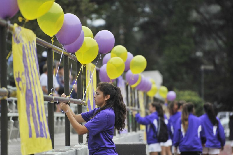 SF State Gators player Karla Uribe and the rest of the women's soccer team decorate the railing at Cox Stadium to honor their graduating players on their last game Thursday, Oct. 30, 2014.