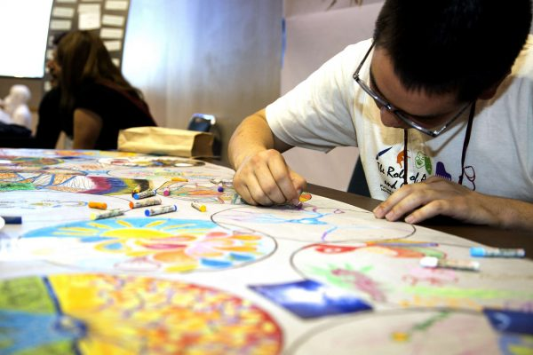 John Fechter, a holistic health intern draws at the art station in Jack Adams Hall at the Future of Healthcare Conference 2014 sponsored by the holistic health department at SF State Saturday, Nov. 8, 2014. Emma Chiang/Special to Xpress.