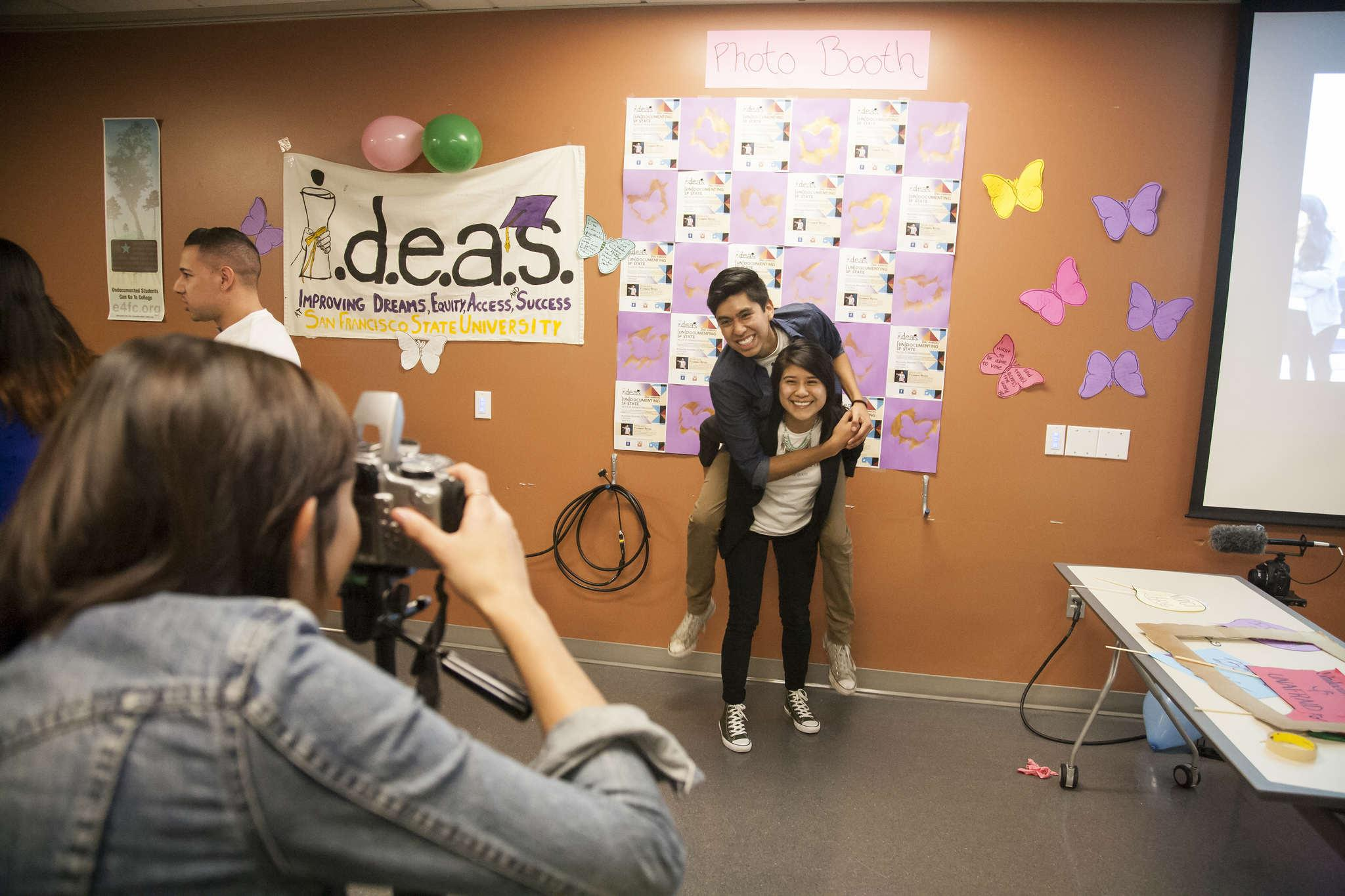 Miguel Castillo and Ana Morales pose for a photo in front of the make shift photobooth at the IDEAS meeting in the library Wednesday, Nov. 12, 2014. Martin Bustamante/Xpress.