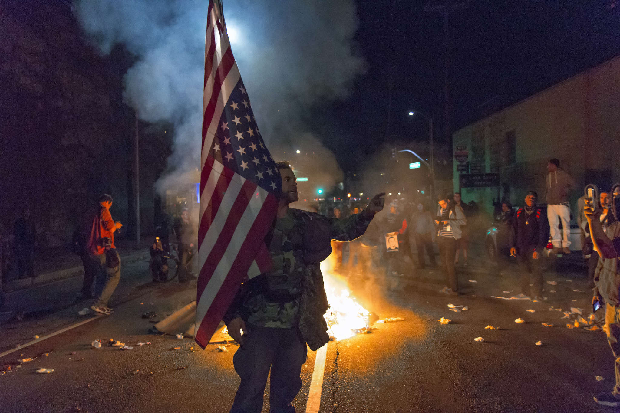 James Cartmill holds an American flag upside-down at the protest in Oakland after a freeway takeover at the Grand Avenue Exit. Protests broke out in the streets of downtown Oakland at Broadway in response to the grand jury's decision not to indict Officer Darren Wilson who shot and killed teenager Michael Brown. Monday, Nov. 24, 2014 in Oakland, Cali. Amanda Peterson/Xpress.