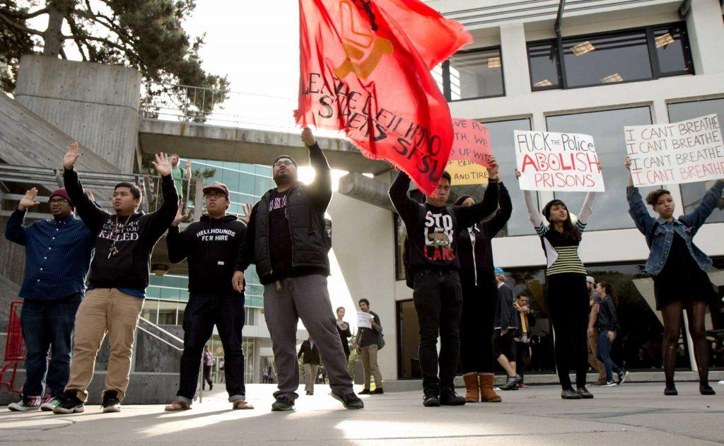 Students with their hands up in protest, join together with the Black and Brown Liberation Coalition and gather at Malcolm X Plaza for a protest against police murders and for unity, justice, equality and peace. The BBLC encouraged students to join in the protest at SF State, Monday, Dec. 8 in San Francisco, Cali.  Amanda Peterson /Xpress