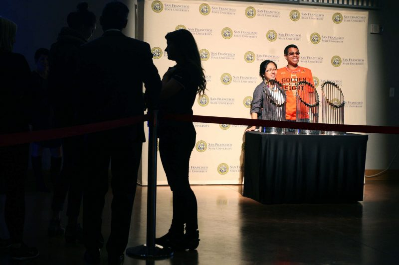 Jose Garcia Ramirez, right, and his girl friend Rosmery Huapaya stand together for a photo with the Giants World Series Trophies in the Cesar Chavez student center Wednesday, Feb. 4.