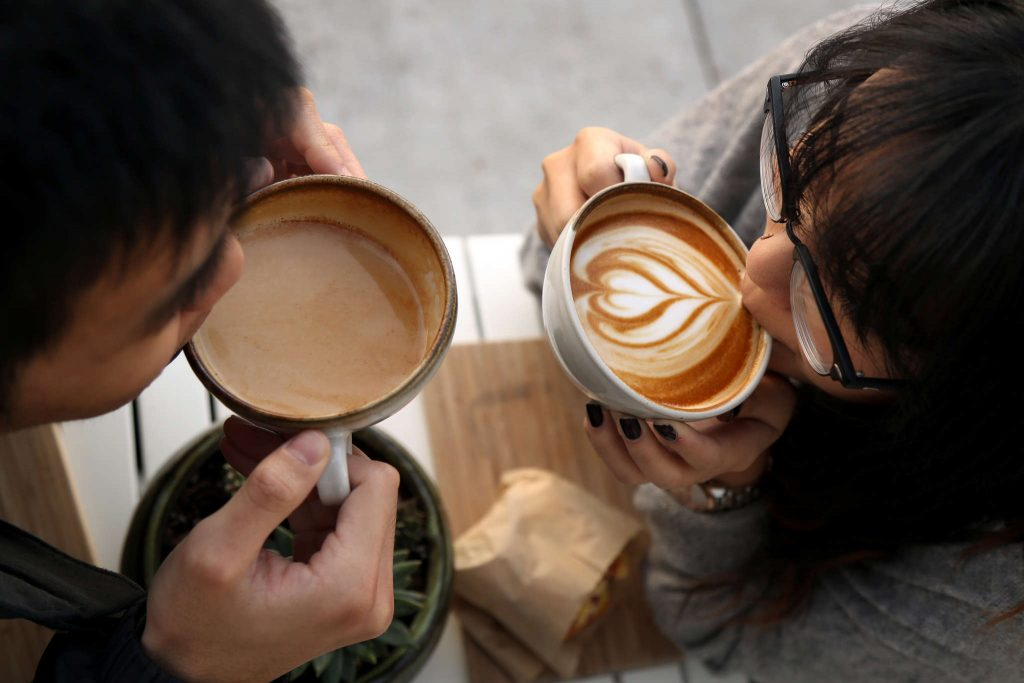 Adrian Chen, BECA major and Tina Huang, international business major drink lattes at Andytown Coffee Roasters in the Outer Sunset of San Francisco on Wednesday Feb 11. One of their favorite ways they enjoy spending time together. (Emma Chiang / Xpress)
